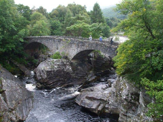 Река спускается к озеру, протекая под старым каменным мостом